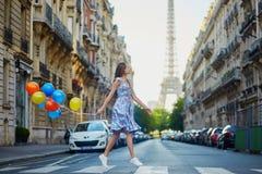 有运行横跨街道的五颜六色的气球的美丽的女孩在巴黎 免版税库存图片