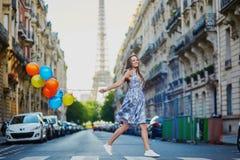 有运行横跨街道的五颜六色的气球的美丽的女孩在巴黎 图库摄影