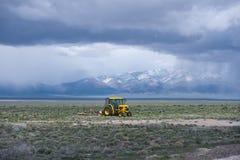有运转在与草的领域的犁的黄色拖拉机 免版税库存图片