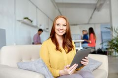 有运转在办公室的片剂个人计算机的红头发人妇女 免版税图库摄影