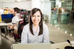 有运转在办公室的耳机的妇女 免版税图库摄影