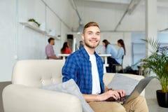 有运转在办公室的膝上型计算机的微笑的人 免版税库存图片
