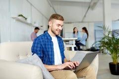 有运转在办公室的膝上型计算机的微笑的人 库存照片
