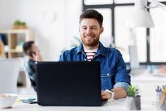 有运转在办公室的膝上型计算机的微笑的创造性的人 图库摄影