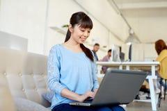 有运转在办公室的膝上型计算机的愉快的亚裔妇女 免版税库存图片