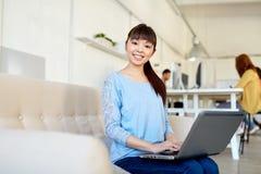 有运转在办公室的膝上型计算机的愉快的亚裔妇女 库存照片