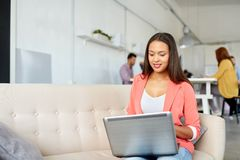 有运转在办公室的膝上型计算机的愉快的妇女 免版税库存照片