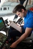 有运转在直升机驾驶舱内的剪贴板的男性航空工程师 库存图片