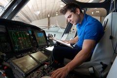 有运转在直升机驾驶舱内的剪贴板的男性航空工程师 库存照片
