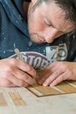 有运转在设计用桌子上的精确度刀子和钢板蜡纸的人 免版税库存图片