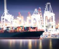 有运转的起重机桥梁的货箱船在黄昏的造船厂 库存图片
