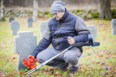 有近拐杖的伤残退伍军人对与花的坟茔纪念碑 免版税图库摄影
