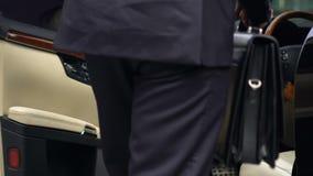 有进入昂贵的黑汽车的公文包的商人,富有的司机 股票视频