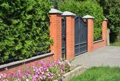有进口、金属门和被整理的绿色Th的绿色篱芭 免版税库存图片