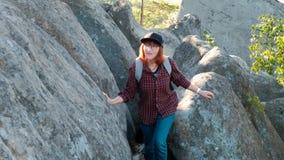 有远足在与太阳的一座山顶部的背包的远足者飘动 少妇健康活跃生活方式 冒险 股票录像