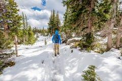 有远足在多雪的足迹的背包的游人 库存照片
