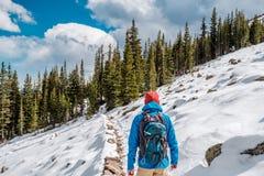 有远足在多雪的足迹的背包的游人 图库摄影