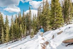 有远足在多雪的足迹的背包的游人 免版税库存图片