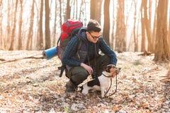 有远足在有他的狗的森林里的背包的年轻人 自然和锻炼概念 库存图片