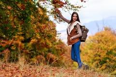 有远足在秋天期间的背包的妇女 免版税库存图片