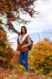 有远足在秋天期间的背包的妇女 免版税库存照片