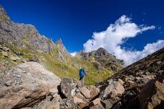有远足在高加索山脉的背包的人在乔治亚 库存图片