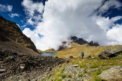 有远足在高加索山脉的背包的人在乔治亚 免版税图库摄影