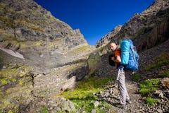 有远足在高加索山脉的背包的人在乔治亚 免版税库存照片