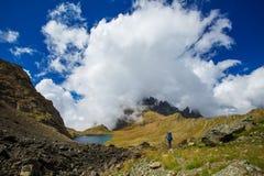 有远足在高加索山脉的背包的人 免版税库存照片