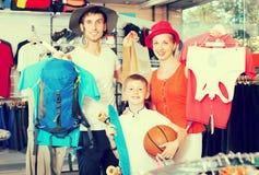 有远足物品的男孩购物的微笑的父母 免版税库存照片