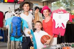 有远足物品的男孩购物的微笑的父母 库存图片
