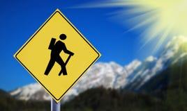 有远足者标志的阿尔卑斯在黄色交通路标签 免版税库存图片