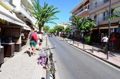 有连续站立反对蓝天散步的热带树的街道 Kos海岛,希腊 库存图片
