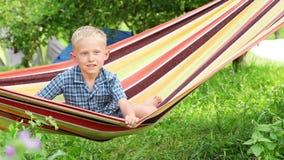 有迷人的微笑的小男孩在吊床 股票视频
