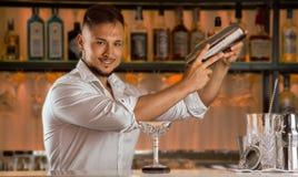 有迷人的微笑的男服务员准备一份可口饮料 免版税库存图片