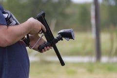 有迷彩漆弹运动枪的人 库存图片
