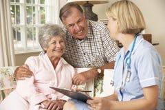有退休的资深的妇女与护士的身体检查在家 免版税库存图片