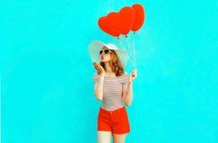 有送在五颜六色的蓝色的红色心形的气球的美丽的年轻女人甜空气亲吻 图库摄影