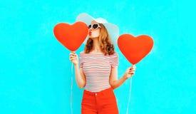 有送在五颜六色的蓝色的红色心形的气球的美丽的年轻女人甜空气亲吻 免版税库存图片