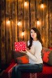 有送在闪烁的背景的礼物盒的可爱的肉欲的年轻女性一个亲吻 库存图片