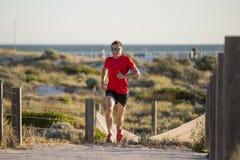 有适合和强的健康身体训练的年轻可爱和愉快的体育赛跑者人在夏天连续锻炼的路轨道 库存照片