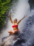 有适合身体实践的瑜伽湿下面热带天堂瀑布小河尖叫的年轻可爱和愉快的妇女激发与 图库摄影