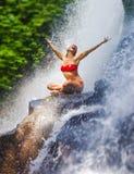 有适合身体实践的瑜伽湿下面热带天堂瀑布小河尖叫的年轻可爱和愉快的妇女激发与 库存照片