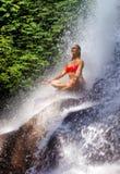有适合身体实践的瑜伽湿下面热带天堂瀑布小河的年轻可爱和愉快的30s妇女在凝思和 库存照片