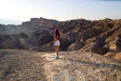 有适合身体的旅客女孩在干燥热的无生命的沙漠风景, Zabriskie点美国前面的白色短的短裤站立 免版税图库摄影