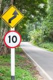 有选择性的限速交通标志10和弯曲道路安全驱动的小心标志在乡下公路在山景森林里 免版税图库摄影