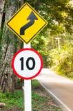 有选择性的限速交通标志10和弯曲道路安全驱动的小心标志在乡下公路 免版税库存图片