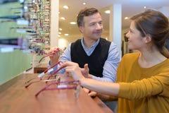 有选择框架的顾客的眼镜师 免版税库存图片