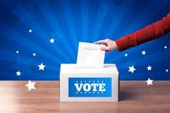 有选票和木箱的手 免版税库存图片