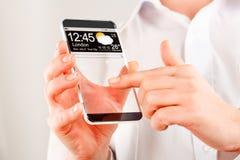 有透明屏幕的智能手机在人的手上。 免版税库存图片